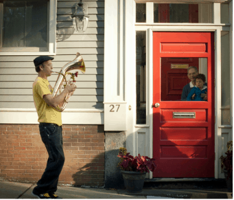 Musician playing to audience behind door